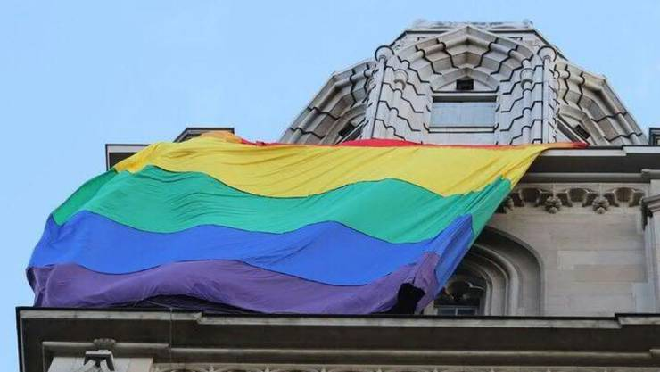 Eine 10 mal 30 Meter grosse Regenbogenfahne hing am Samstag als Zeichen gegen Hass am Nordturm des Zürcher Grossmünsters.