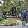 Menschen stehen am Grab des tschechischen Sängers Karel Gott auf dem Malvazinky-Friedhof, wo frische Blumen stehen und Kerzen brennen. Vor einem Jahr, am 1. Oktober 2019, war der Sänger im Alter von 80 Jahren gestorben. Foto: Michael Heitmann/dpa