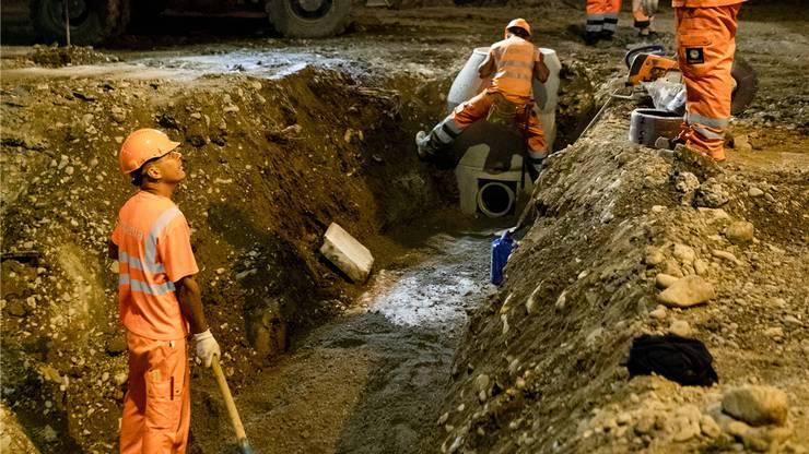 Auf dem Grund angekommen: Hier verlegen die Arbeiter ein Rohr, das unter dem Limmattalbahn- Trassee verläuft.