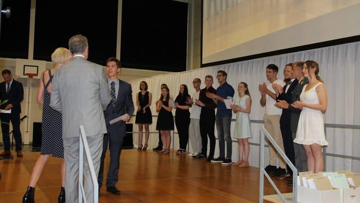 Gastrednerin Margrit Stamm (l.) und Rektor Paul Knoblauch (vorne) überreichten den besten Absolventinnen und Absolventen ihr Berufsmatura-Zeugnis.