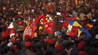 Anhänger von Hugo Chávez tragen seinen mit Kleidungsstücken übersähten Sarg zur Militärakademie, wo der Leichnam bis zur Trauerfeier aufgebahrt wird