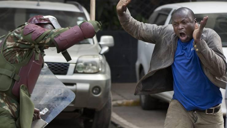 Ein Polizist schlägt einen Mann Holzknüppel während einer Demonstration der Opposition in Kenias Hauptstadt Nairobi.