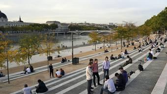 Menschen sitzen entlang des Flusses Rhone. Die französischen Behörden haben die Stadt Lyon auf die höchste Warnstufe gesetzt. Versammlungen sind untersagt und Bars werden schließen müssen. Foto: Laurent Cipriani/AP/dpa