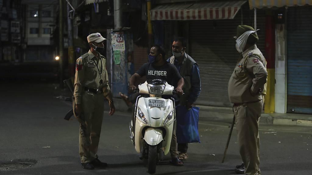 Polizisten kontrollieren einen Rollerfahrer: Dutzende Städte in Indien haben als Maßnahme zur Eindämmung der Coronavirus-Pandemie Ausgangssperren verhängt. Foto: Channi Anand/AP/dpa