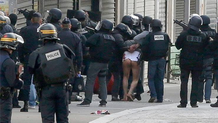 Die Sicherheitskräfte führen nach der Erstürmung der Wohnung in Saint-Denis einen Verdächtigen ab. Sie werden verdächtigt einen Angriff aufs Geschäftsviertel La Défense geplant zu haben.Jacky Naegelen/reuters
