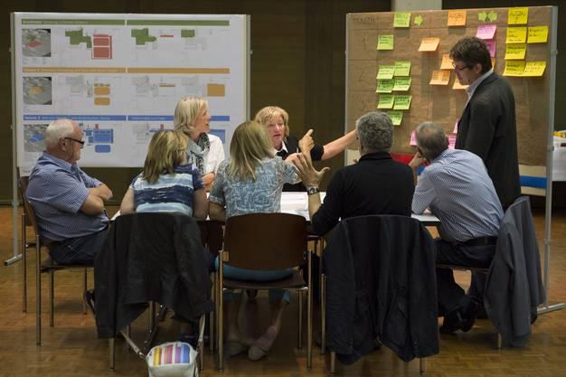 Eine Tischgruppe diskutiert die Varianten