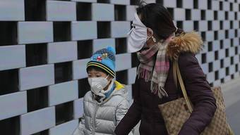 Die durch das Coronavirus hervorgerufene Lungenkrankheit aus China verbreitet sich weiter - überall auf der Welt schützen sich Menschen mittlerweile wie hier im Bild in Peking mit Schutzmasken.