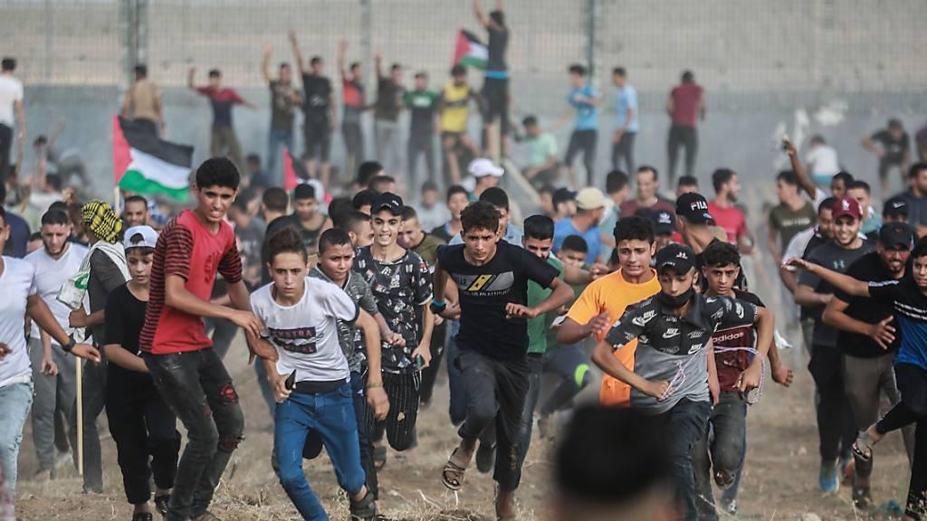 Palästinensische Demonstranten stoßen mit israelischen Sicherheitskräften zusammen, nachdem sie am Grenzzaun zu Israel östlich von Gaza-Stadt gegen die israelische Belagerung des palästinensischen Streifens protestiert haben. Foto: Mohammed Talatene/dpa