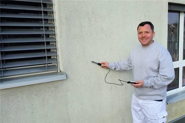 Malermeister Felix Pratter misst die Feuchtigkeit einer Fassade.