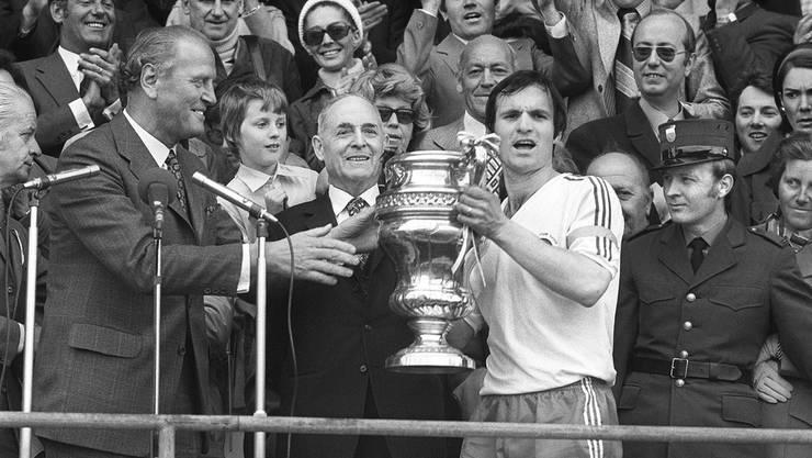 Fernand Luisier, Captain des FC Sion, nimmt am 15. April 1974 nach dem Cupfinal gegen Neuchatel Xamax im Stadion Wankdorf in Bern den Pokal aus den Händen des Bundesrates Willi Ritschard entgegen. Der FC Sion gewann den Final 3:2.