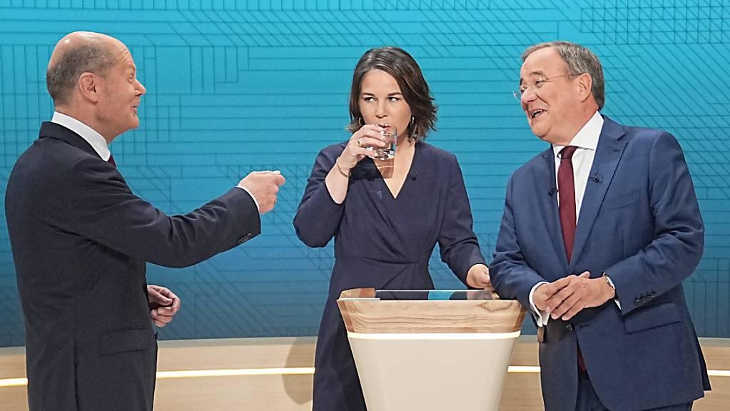 Kanzlerkandidat Olaf Scholz (SPD, l-r), Kanzlerkandidatin Annalena Baerbock (Bündnis90/Die Grünen) und Kanzlerkandidat Armin Laschet (CDU) stehen im Fernsehstudio. Laut einer von der CDU in Auftrag gegebenen Zuschauerbefragung hat Laschet beim zweiten Triell knapp am meisten positiv überrascht. Foto: Michael Kappeler/dpa-Pool/dpa