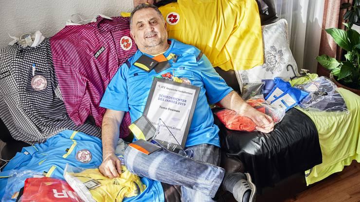 Tuma Oezmen posiert mit seiner Schiedsrichter-Trikot-Sammlung.