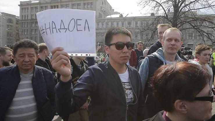 """Anti-Putin-Demonstranten im Zentrum Moskaus halten Transparente mit der Aufschrift """"Nadojel"""" hoch - deutsch etwa: """"Wir haben genug/Wir sind es leid""""."""