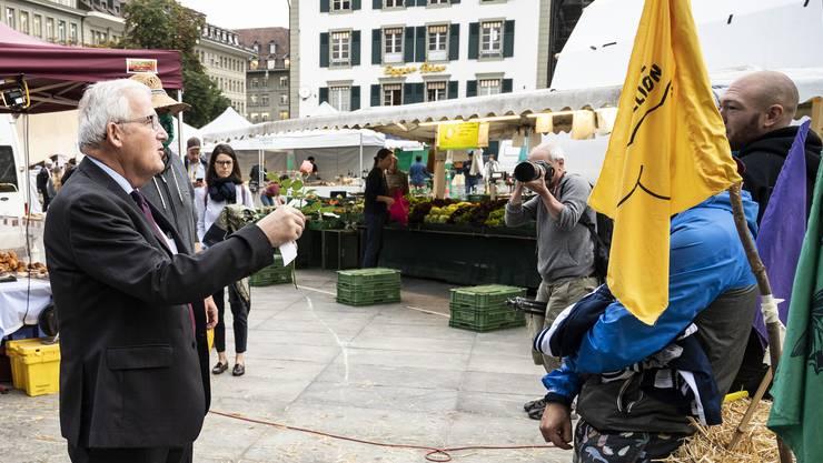 Zur Beruhigung der Gemüter: Klimaaktivisten beschenken den Ständeratspräsidenten Hans Stöckli, mit  einer Rose.