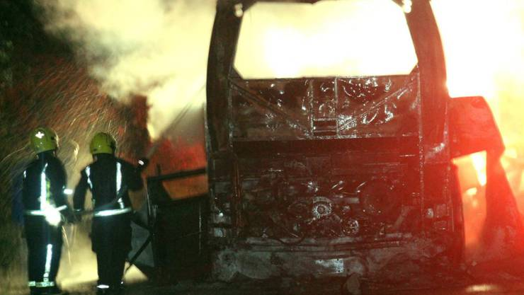 Mexikanische Feuerwehrleute versuchen den in Brand geratenen Reisebus zu löschen. Bei dem Unglück kamen mindestens 20 Menschen ums Leben.