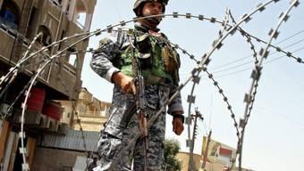 Ein irakischer Polizist bewacht ein Wahllokal in Bagdad