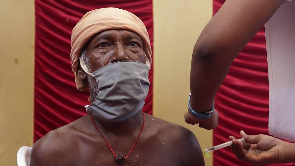 ARCHIV - Ein Mitarbeiter des Gesundheitswesens in Indien impft einen Mann in einem Impfcamp mit einer Dosis des Corona-Impfstoffs Covaxin. Foto: Sri Loganathan/ZUMA Wire/dpa