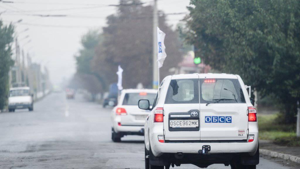 Fahrzeuge der Beobachtermission der OSZE nördlich von Donezk in der Ostukraine. Am Sonntag wurde ein OSZE-Beobachter getötet, als ein OSZE-Fahrzeug auf eine Mine fuhr. (Archiv)