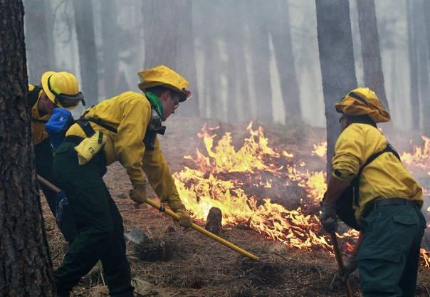 Feuerwehrleute versuchen, die Flammen zu ersticken