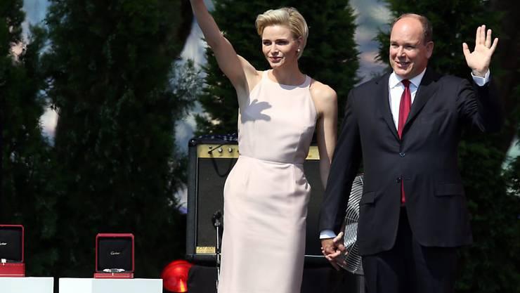 Fürst Albert II und seine Frau Charlène winken der Menge zu