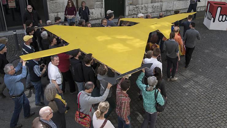Die Gruppe für eine Schweiz ohne Armee beschliesst den Kampf gegen die Neubeschaffung von Kampfjets und versenkt einen Jet aus Pappe in einer Abstimmungsurne.