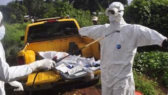 Ein Ebola-Helfer desinfiziert in Monrovia, Liberia einen Kollegen