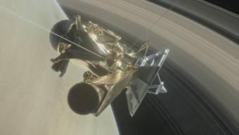 """Die Raumsonde """"Cassini"""" zwischen dem Saturn und einem seiner Ringe (in einer Illustration der NASA)."""