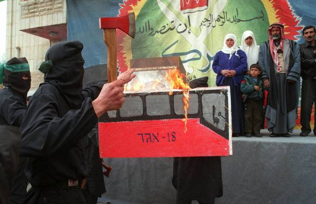 Militante Palästinenser verbrennen zwei Jahre nach Ajaschs Tod symbolisch einen israelischen Bus der Linie 18 – eine von Ajaschs Bomben hatte einen solchen Bus zerfetzt. Im Hintergrund Ajaschs Familie.