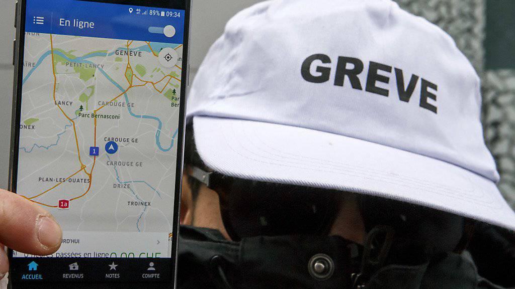 Ein streikender Chauffeur zeigt am Mittwoch vor dem Genfer Sitz von Uber in Carouge die Smartphone-Applikation des Fahrdienstes.