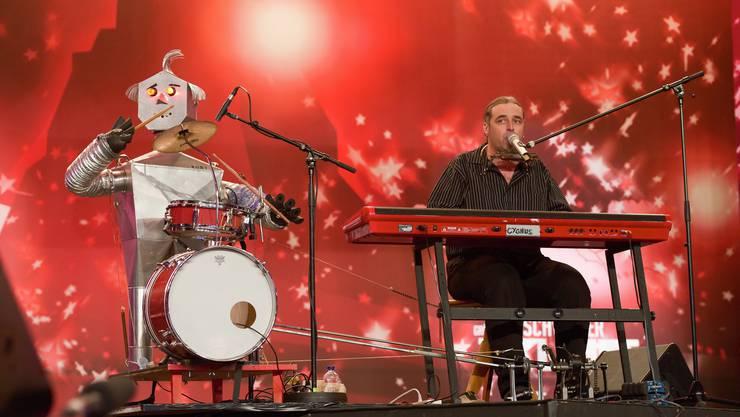 Franz hat ein Ein-Mann-Orchester mit einem Blechroboter, der Schlagzeug spielt.