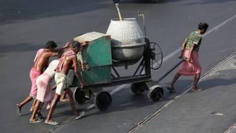 Indische Arbeiter am Donnerstag in Kalkutta beim Schieben eines Betonmixers in brütender Hitze