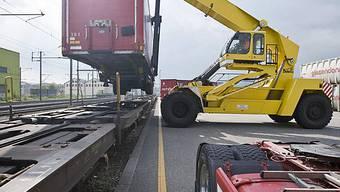 Mit einem fahrbaren Kran werden Container von der Strasse auf die Schiene verladen (Archiv)