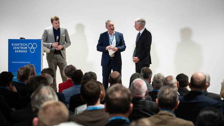 Markus Bürgin (Mitte) und der Experte des HTZ Reto Eggimann (links), erklären Moderator Herbert Scholl und dem Publikum, wie die Reinigung eines Kessels mithilfe von Explosionen vor sich geht.