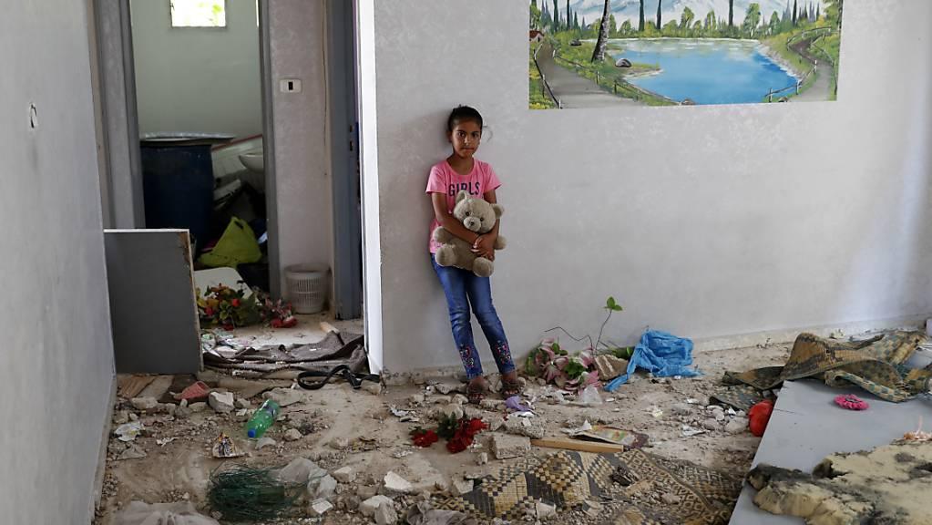 Die 10-jährige Rahaf Abu Fares, die vier Familienmitglieder verlor, als ihr Haus während des elftägigen Gefechts zwischen Israel und der Hamas im Mai von israelischer Artillerie bombardiert wurde, trägt einen Teddybär inmitten der Trümmer ihres Hauses im Beduinendorf Umm Al-Nasr. Foto: Adel Hana/AP/dpa