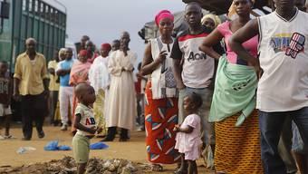Wählerinnen und Wähler stehen in Abidjan Schlange.