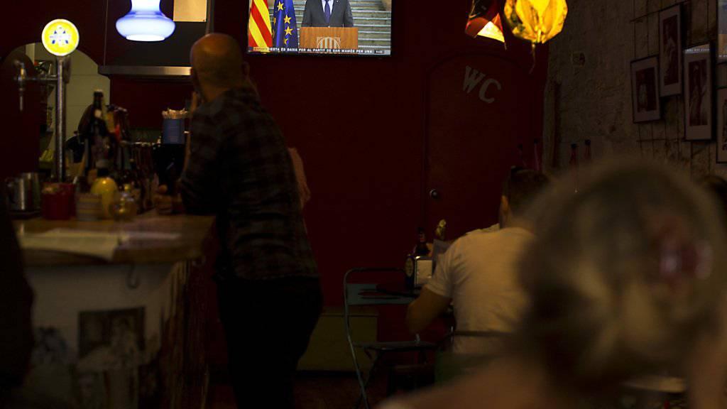 Barbesucher hören sich Puigdemonts Fernsehrede an. In den spanischen Medien wurde die Rede so interpretiert, dass er der Amtsenthebung nicht Folge leisten wolle.