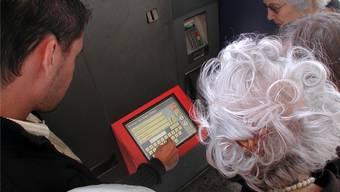 Ein BLS-Mitarbeiter erklärt einer Gruppe Senioren die Bedienung eines Billettautomaten.
