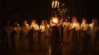 Das Mädchen, welches die Rolle der heiligen Lucia übernimmt, hat fünf an einer Krone befestigte Kerzen auf dem Kopf.