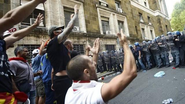 Aufgebrachte Arbeiter versuchen die Polizeisperre zu durchbrechen