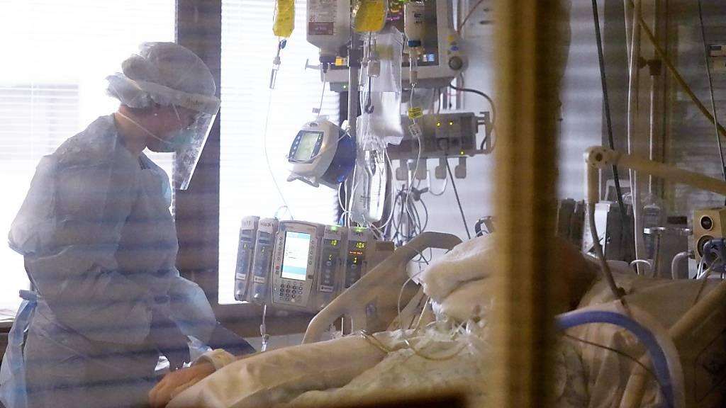 Eine Krankenpflegerin behandelt einen Patienten auf der Corona-Intensivstation im UW Medical Center-Montlake in Seattle. Foto: Elaine Thompson/AP/dpa