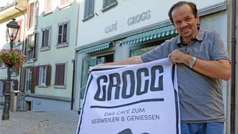 Klaus Kaiser präsentiert sein Logo vor dem Café.