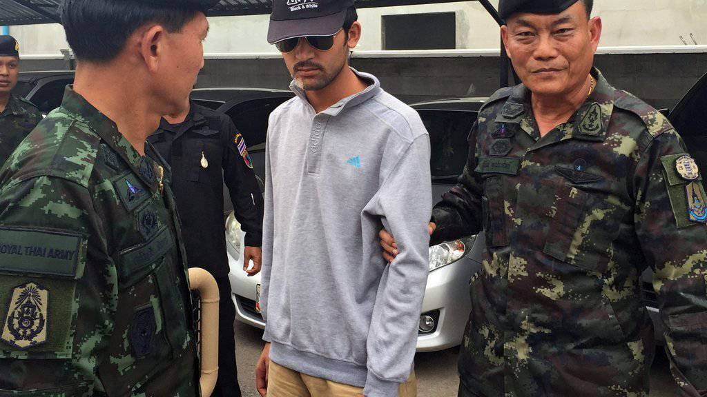 Der mutmassliche Bombenleger wird von thailändischen Sicherheitskräften abgeführt. Er soll aus der Unruheregion Xinjiang in Nordwestchina stammen
