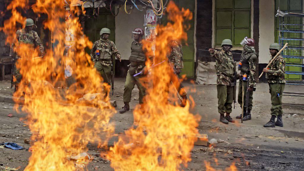 Einsatzkräfte hinter brennenden Barrikaden in Nairobi