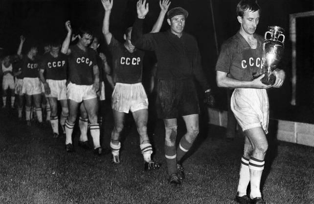 EM 1960: Die sowjetische Mannschaft (UdSSR) schreitet nach ihrem 2:1-Sieg über Jugoslawien im Final m Parc des Princes in Paris in einer Reihe jubelnd über den Rasen. Lew Jaschin, der Torhüter der Mannschaft (2. von rechts) winkt zusammen mit den anderen Spielern hinter dem Captain Igor Netto, der den Pokal trägt, den Zuschauern zu.