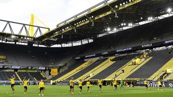 Skurril: Die Dortmunder Spieler feiern den Derbysieg vor der leeren Stehplatztribüne.