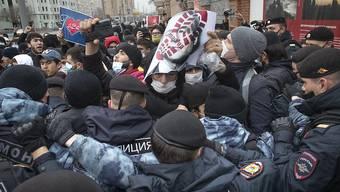 Die Polizei blockiert Mundschutz tragende Demonstranten, welche mit einem Plakat, das einen Fußabdruck auf dem Gesicht des französischen Präsidenten Macron zeigt, gegen die Veröffentlichung von Karikaturen in Frankreich, die den Propheten Mohammed darstellen, protestieren. Foto: Pavel Golovkin/AP/dpa