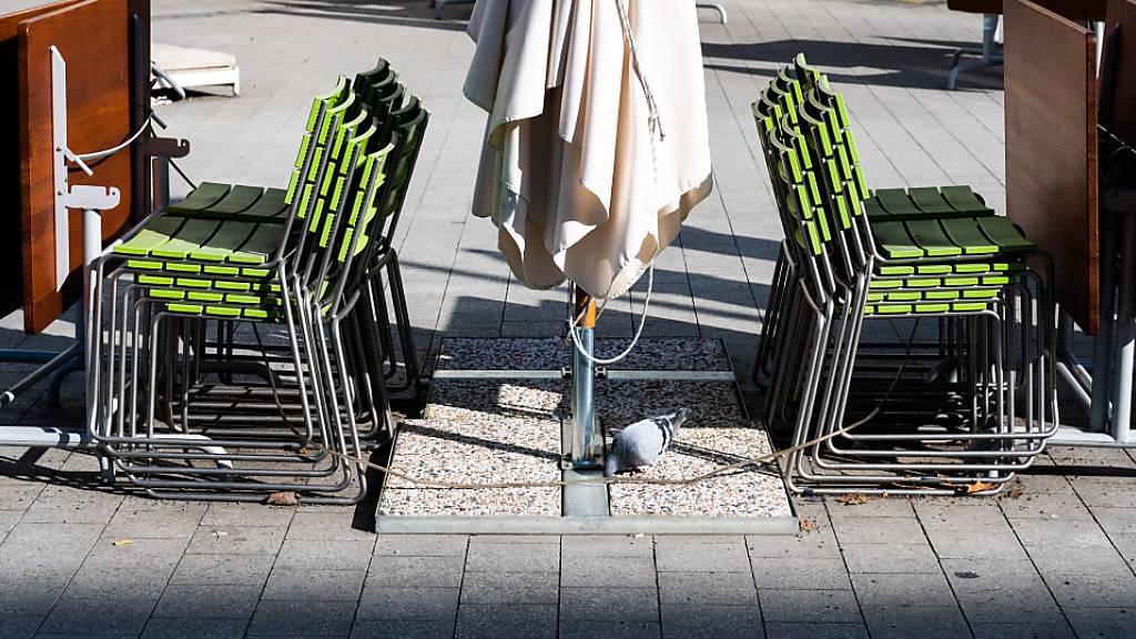 Gestapelte Stühle und zusammengeklappte Tische stehen in der Außengastronomie eines geschlossenen Restaurants in der Hannoveraner Innenstadt. Foto: Julian Stratenschulte/dpa