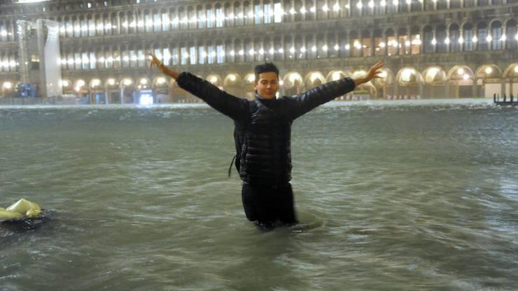 Ein Mann steht auf dem überfluteten Markusplatz in Venedig. (Archivbild)
