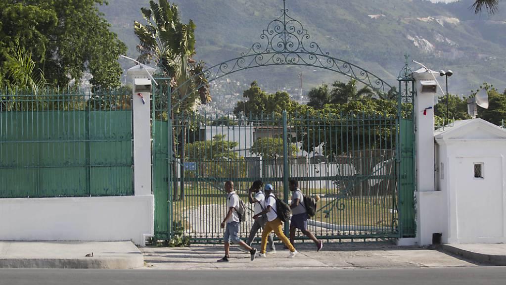 Fußgänger gehen am Tor des Präsidentenpalast vorbei. Präsident Moise war in der Nacht zum Mittwoch gegen 1.00 Uhr (Ortszeit) in seiner Residenz erschossen worden. Trotz erster Festnahmen ist die Lage in Haiti weiterhin angespannt.