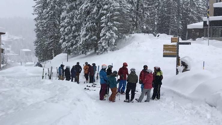 Skifahrer warten am Sonntagmorgen in Arosa auf den Start der Bahnen.